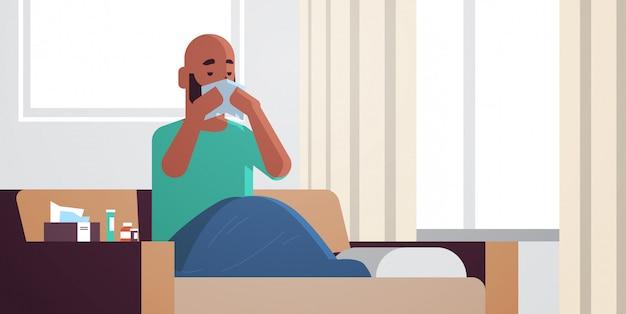 Kranker mann bläst nase mit taschentuch ungesunden afroamerikaner kerl reinigung rotznase mit grippe niesen sitzen auf sofa krankheit konzept modernes wohnzimmer interieur horizontal