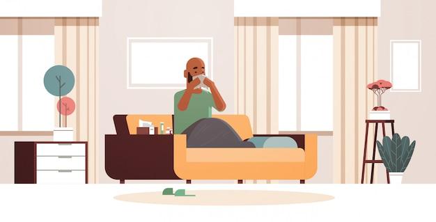 Kranker mann bläst nase mit taschentuch ungesunden afroamerikaner kerl reinigung rotznase mit grippe niesen sitzen auf sofa krankheit konzept modernes wohnzimmer interieur in voller länge horizontal