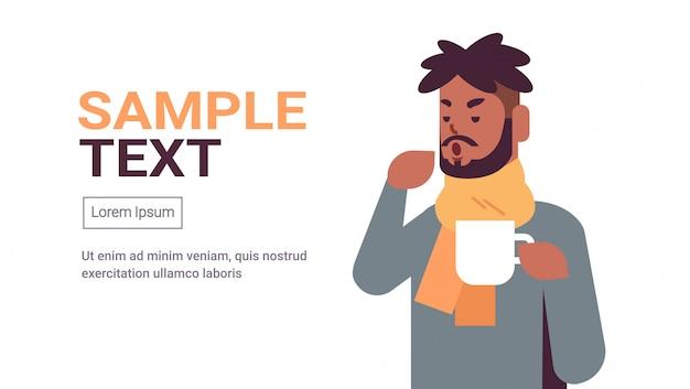Kranker mann, der niesen trinkt heißen tee ungesunden afroamerikaner kerl im schal, der an kaltem grippevirus-krankheitskonzept leidet, flacher porträtkopierraum horizontal