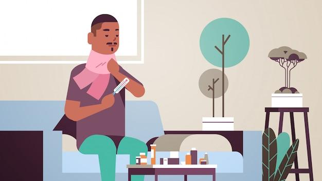 Kranker mann, der temperatur mit thermometer ungesunden afroamerikaner kerl im schal leidet, der an kaltem grippevirus-krankheitskonzept leidet modernes wohnzimmerinnenraum flaches porträt horizontal