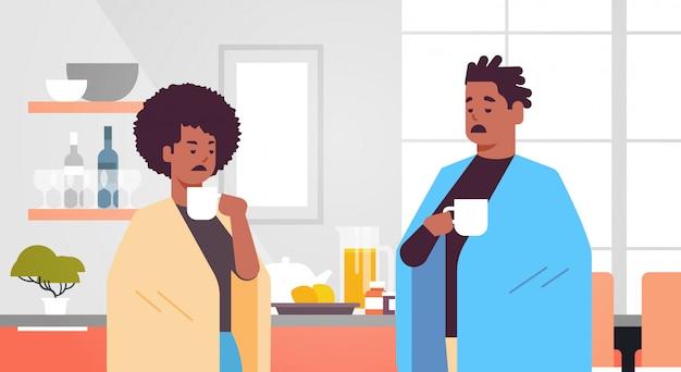 Krankes paar, das heißen tee trinkt ungesunde afroamerikanische mannfrau bedeckt mit decke, die an erkältungsgrippeviruskrankheit leidet