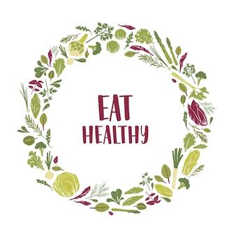 Kranz aus grünen pflanzen, salatblättern, gemüse, kräutern und eat healthy slogan im inneren