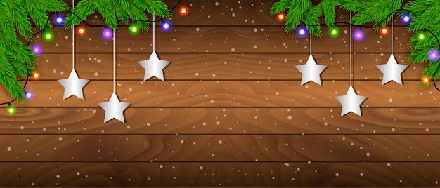 Kreativer rahmen aus weihnachtstannenzweigen auf hölzernem hintergrund mit weihnachtslichtern. weihnachts- und neujahrsthema