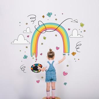 Künstlerisches kleines mädchen, das einen wunderbaren regenbogen malt