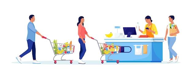 Kunden stehen im supermarkt mit waren im einkaufswagen schlange. frau legte käufe an der kasse zum bezahlen. warteschlange im store. lebensmitteleinkäufe