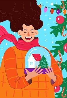 Lachende frau mit schneekugel mit haus und weihnachtsbaum in frohe weihnachten und guten rutsch ins neue jahr
