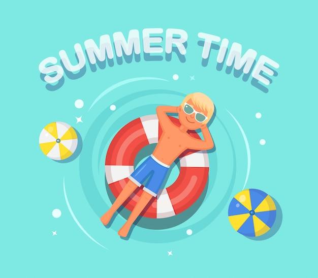Lächeln mann schwimmt, bräunen auf luftmatratze, rettungsboje im schwimmbad. junge, der auf strandspielzeug, gummiring schwimmt. unfähiger kreis auf dem wasser. sommerferien, ferien, reisezeit.