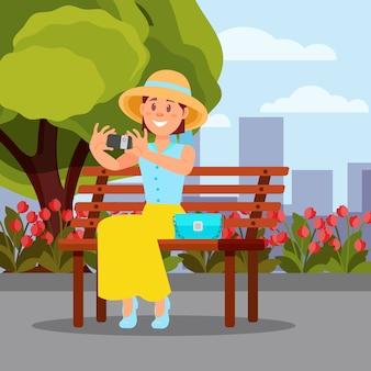Lächelnde frau, die auf holzbank sitzt und selfie macht. grüner baum, blühende blumen und stadtgebäude auf hintergrund. flache landschaft