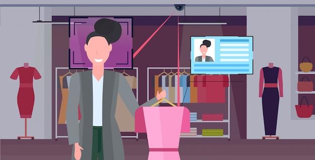 Lächelnde frau hält kleid kunden gesichtserkennung konzept überwachungskamera überwachung cctv-system mode boutique innenporträt horizontal