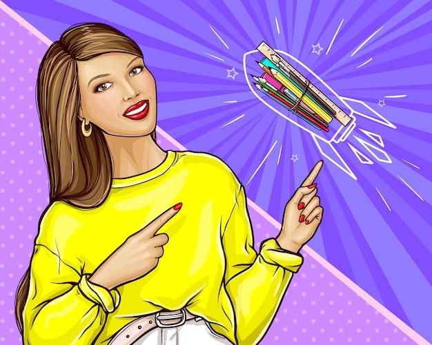 Lächelnde frau im gelben sweatshirt, das auf briefpapier, pop-art-illustration zeigt. werbebanner für grafikstudio-, bildungs- oder kunstkurse. zurück in die schule oder willkommen im schulkonzept mit dem lehrer