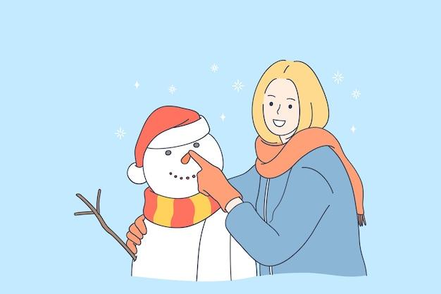 Lächelnde frau zeichentrickfigur, die schneemann macht und winterzeit genießt