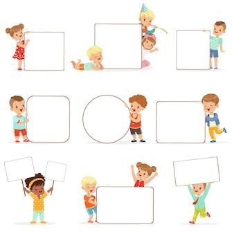 Lächelnde kinder, die mit weißen leeren brettern stehen. glückliche kleine jungen und mädchen in der freizeitkleidung, die leere plakatillustrationen hält