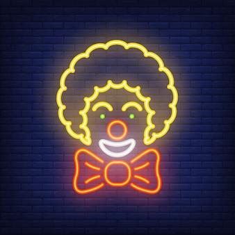 Lächelnde neonikone des clowns. zirkuskünstler mit großem bogen auf dunklem backsteinmauerhintergrund.