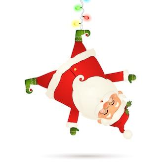 Lächelnde weihnachtsmann-karikaturfigur, die kopfüber mit girlandenschnur der funkelnden lichter mit mehrfarbigen glühbirnen auf weißem hintergrund lokalisiert hängt. weihnachtsmann klausel für winter- und neujahrsferien.
