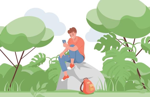 Lächelnder junge, der auf dem felsen sitzt und mit jemandem auf einem smartphone spricht.