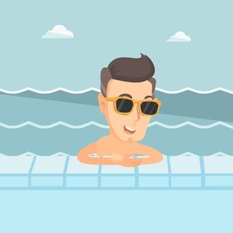 Lächelnder junger mann im swimmingpool.