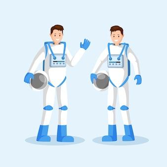 Lächelndes astronautenteam, zwei männer in den raumanzügen, die hand wellenartig bewegen und sturzhelme halten