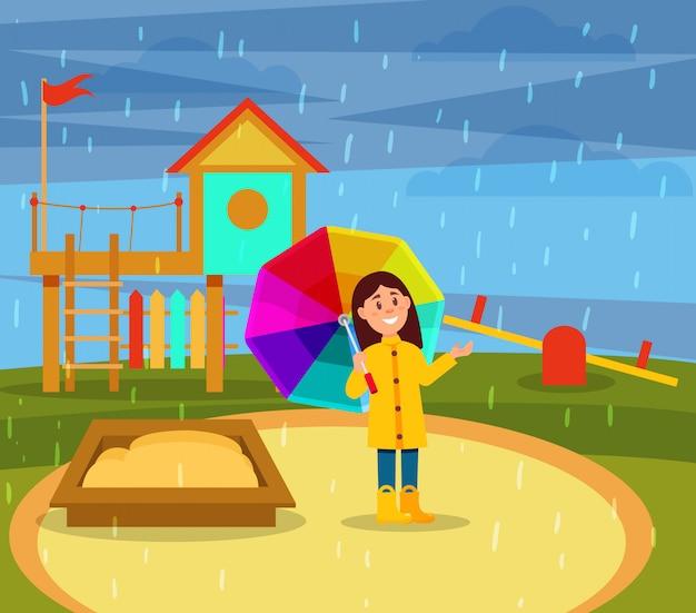 Lächelndes kleines mädchen im gelben regenmantel, der mit regenbogenregenschirm auf spielplatz in regnerischer tagesillustration geht