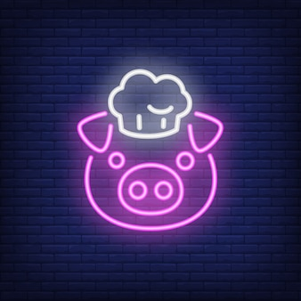 Lächelndes schwein im chefhut. leuchtreklame element. nacht helle werbung.