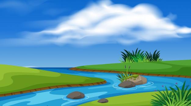 Landschaft mit fluss und grünem feld