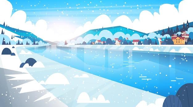 Landschaft von winterdorf-häusern nahe gebirgshügeln und dem gefrorenen fluss oder see
