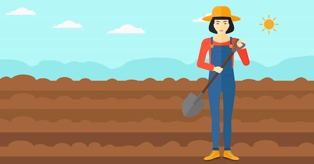 Landwirt auf dem feld mit schaufel.