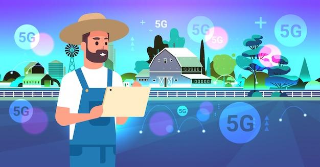 Landwirt, der tablette 5g online drahtloses systemverbindungsorganisation der ernte des intelligenten landwirtschaftskonzepts farmgebäude-landschaftshintergrund-horizontales porträt flach verwendet