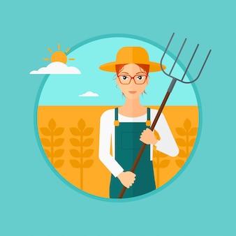 Landwirt mit heugabel auf dem weizengebiet.