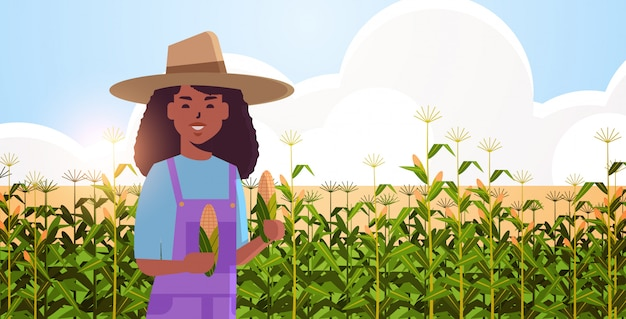 Landwirtin, die maiskolben-afroamerikaner-landfrau in overalls hält, die auf maisfeld bio-landwirtschaft landwirtschaft landwirtschaft erntezeit konzept flaches porträt horizontal stehen