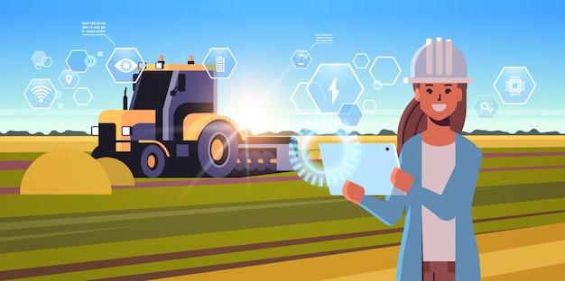 Landwirtin mit tablette, die traktorpflugfeld intelligente landwirtschaft moderne technologieorganisation des ernteanwendungskonzeptes landschaftsporträt steuert