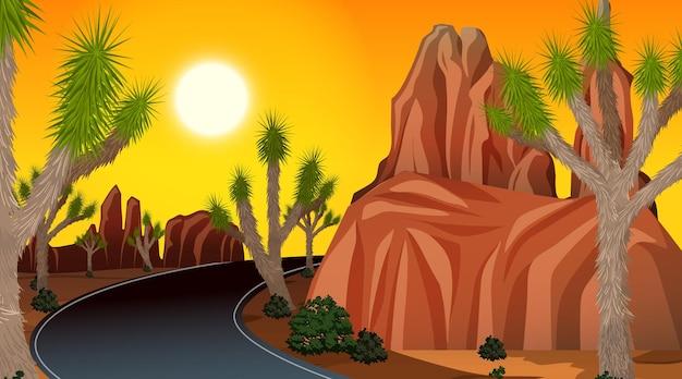 Langer weg durch die wüstenlandschaftsszene zur sonnenuntergangszeit