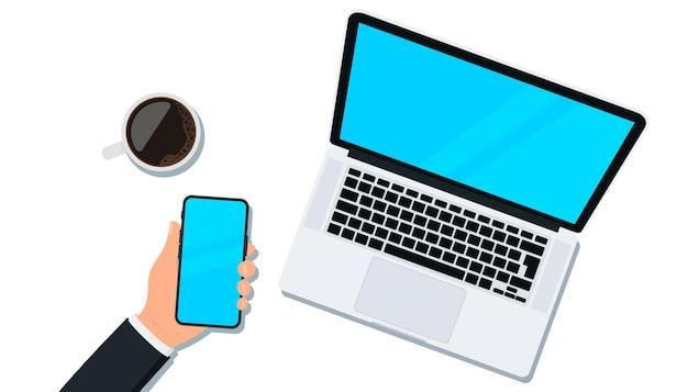 Laptop-computer. computer-notizbuch. hand hält smartphone. leerer kopienraum, der arbeitsprozess symbolisiert. sicht von oben. arbeitsplatz für business, management und it. laptop, handy und kaffeetasse