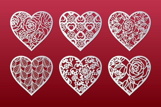Lasergeschnittener satz gemusterter herzen mit rosen, blättern und blumen. valentinstagskartenentwurf.