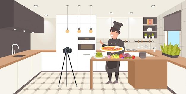Lebensmittel-blogger in uniform kochen pizza in der küche männlicher koch aufnahme video-blog mit kamera auf stativ blogging-konzept mann vlogger erklären, wie man ein gericht horizontal in voller länge kochen