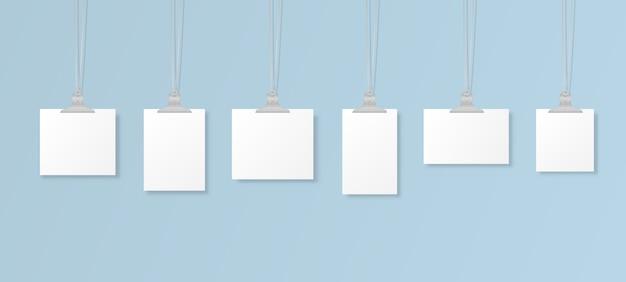Leere hängende fotorahmen oder plakatvorlagen auf hintergrund. eine reihe von weißen plakatmodellen, die am ordner an der wand hängen. rahmen für ein blatt papier. illustration.