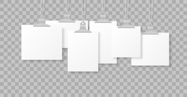 Leere hängende fotorahmen oder plakatvorlagen lokalisiert auf hintergrund. ein satz weißes plakat, das auf binder an der wand hängt. rahmen für ein blatt papier. illustration.