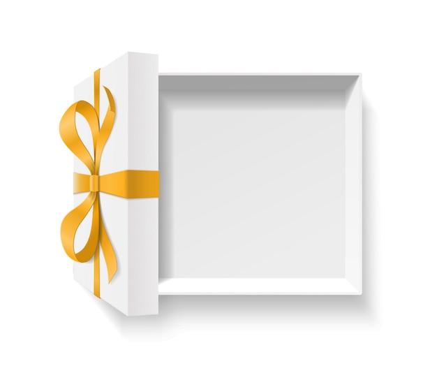 Leere offene geschenkbox mit goldener farbe schleifenknoten, band auf weißem hintergrund. alles gute zum geburtstag, weihnachten, neujahr, hochzeit oder valentinstag paketkonzept. abbildung, draufsicht