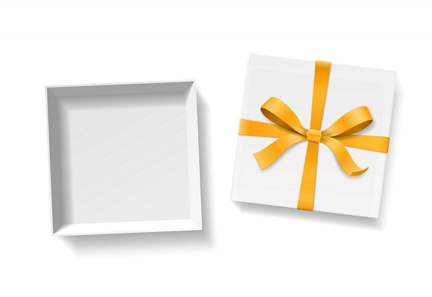 Leere offene geschenkbox mit goldfarbenem schleifenknoten und band auf weißem hintergrund. alles gute zum geburtstag, weihnachten, neujahr oder valentinstag paketkonzept. nahansicht der draufsicht