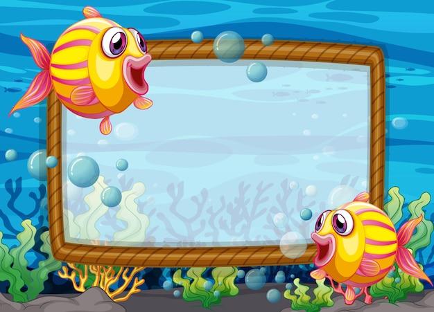 Leere rahmenschablone mit zeichentrickfigur der exotischen fische in der unterwasserszene Premium Vektoren