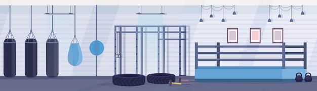 Leere ringboxarena mit boxsäcken verschiedener formen für das üben von kampfkünsten in der horizontalen fahne des modernen kampfklubinnenraums