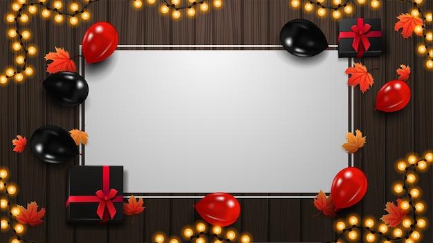 Leere vorlage des schwarzen freitags mit roten und schwarzen luftballons, geschenken, weißem papierblatt, girlandenrahmen, ahornblättern und hölzernem hintergrund, draufsicht