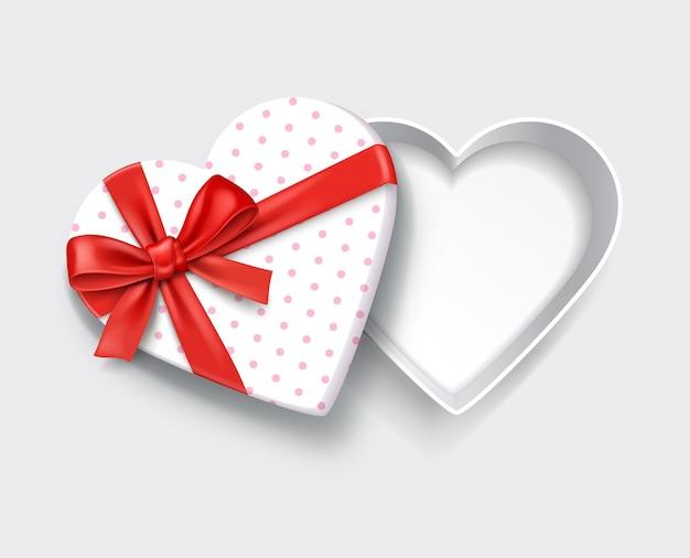 Leere weiße geschenkbox in form eines offenen herzens mit rotem band.