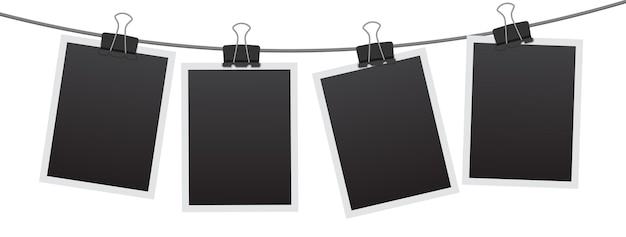 Leerer sofortbildrahmen, der an einem clip hängt. schwarze leere weinlesebilderrahmenschablone lokalisiert auf weißem hintergrund.