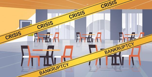 Leeres geschlossenes café mit gelbem insolvenzkrisenband coronavirus-pandemiequarantäne