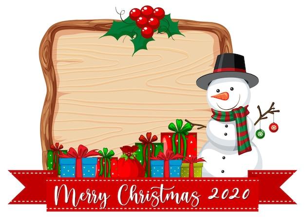 Leeres holzbrett mit frohe weihnachten 2020 nachricht und schneemann