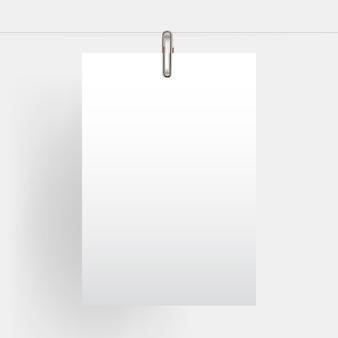 Leeres vertikales papier, das realistischen spott oben mit goldbüroklammer hängt
