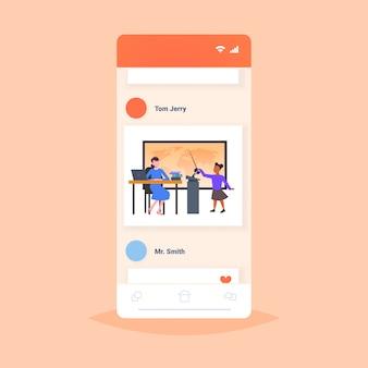 Lehrer mit schüler schulmädchen zeigt auf weltkarte geographie lektion am schulbildungskonzept modernes klassenzimmer in voller länge smartphone-bildschirm online-mobilanwendung