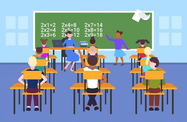 Lehrerin mit schülern, die an schreibtischen sitzen und das schulmädchen betrachten, das mathematisches problem an der tafel-schulunterrichtsbildungskonzept-modernen schulklassenrauminnenraum in voller länge horizontal löst