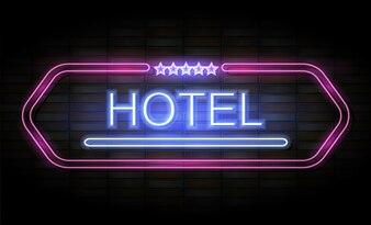 Leuchtreklame des Hotels auf Backsteinmauer