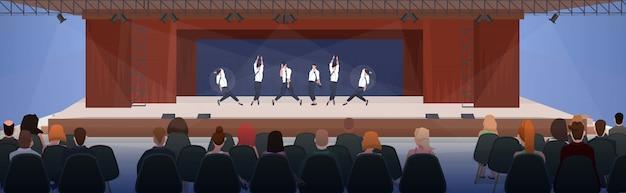 Leute, die auf stühlen sitzen und bei der aufführungstanzgruppe zuschauen, die auf der bühne mit vorhängen modernes konzept halle innen horizontale wohnung tanzen